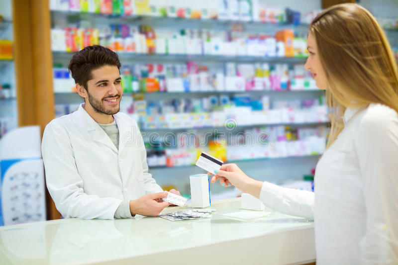 Experienced pharmacist counseling female customer stock photos