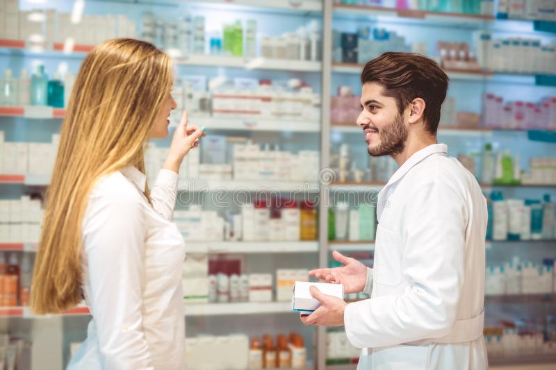 Experienced pharmacist counseling female customer in pharmacy. Experienced pharmacist counseling female customer in modern pharmacy royalty free stock photo