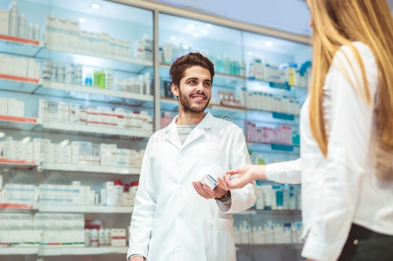 Experienced pharmacist counseling female customer in pharmacy stock photo
