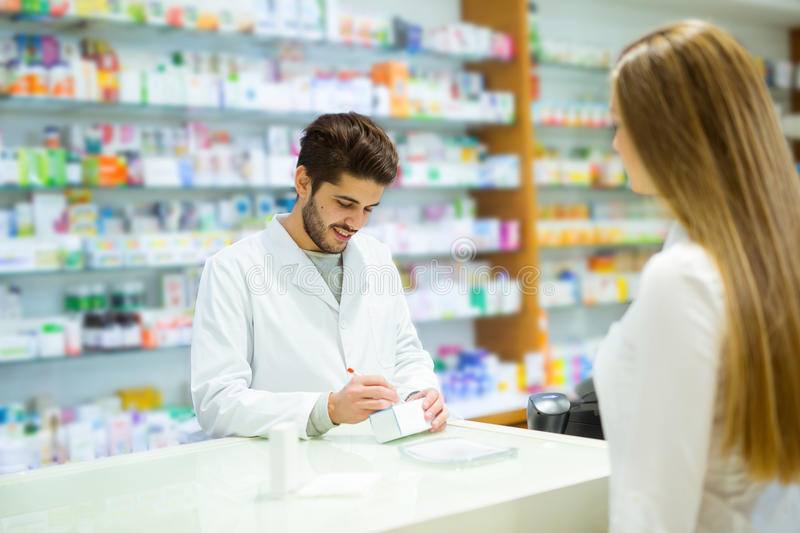 Experienced pharmacist counseling female customer in pharmacy. Experienced pharmacist counseling female customer in modern pharmacy royalty free stock image