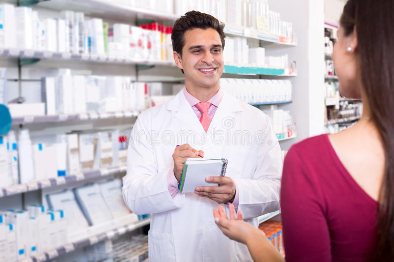 Experienced pharmacist counseling female customer. Smiling experienced pharmacist counseling female customer stock photos