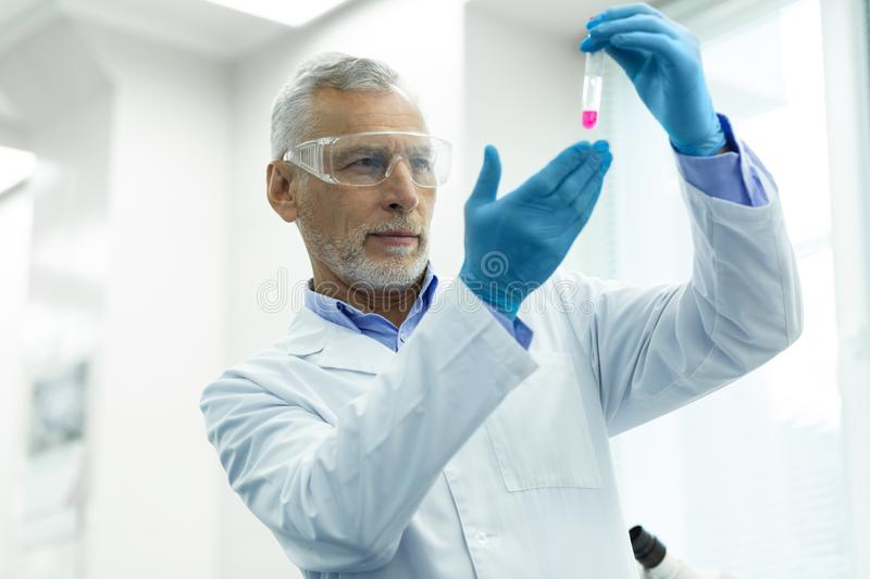 Attentive mature male person working in laboratory. Experienced professor. Handsome scientist wrinkling his forehead while checking reagent before experiment stock image
