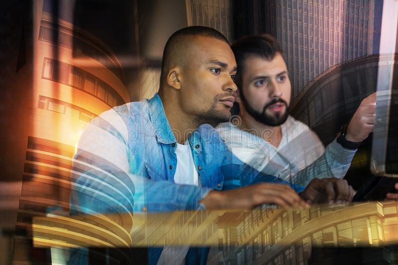 Experienced programmers looking at the screen while working together. Smart specialists. Clever attentive programmers sitting in front of a modern computer and royalty free stock images