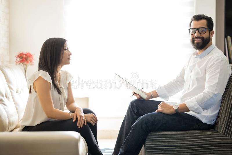 Experienced psychotherapist with female patient in office. Happy hispanic male psychologist with female patient sitting on sofa in his office stock photos