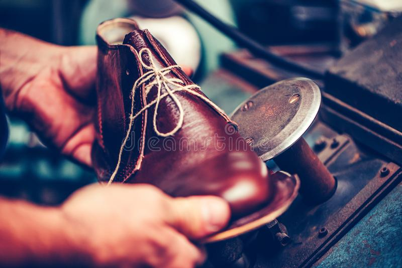 Experienced shoemaker using special machine tool for making a shoes royalty free stock photos