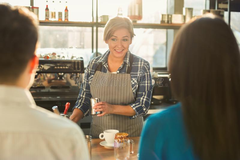 Experienced smiling barista making coffee to customers royalty free stock photo