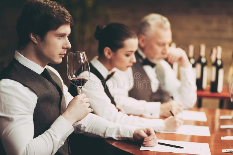 Experienced sommelier explores taste of wine in restaurant. Young waiter tastes alcoholic beverages. Checking taste, color, sediments of wine stock photo