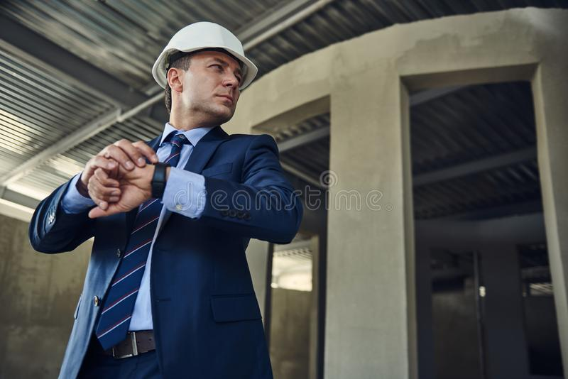 Experienced supervisor is looking on construction site. Waist up portrait of adult project manager is standing and checking time while using smartwatch. Copy royalty free stock images