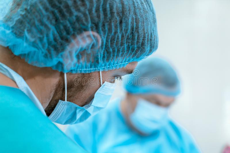 An experienced surgeon in a mask and gown operates in a sterile operating room with an assistant and an anesthesiologist..A group royalty free stock photo