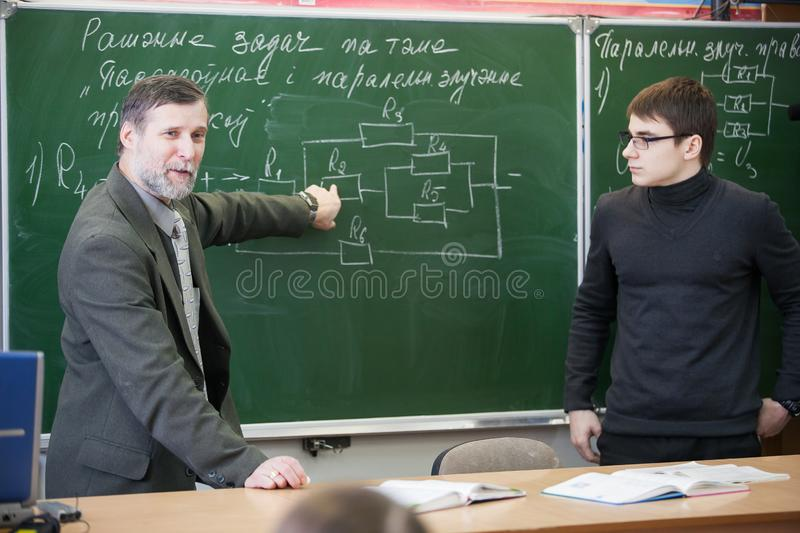 Experienced teacher giving comments on teenage boy work stock images