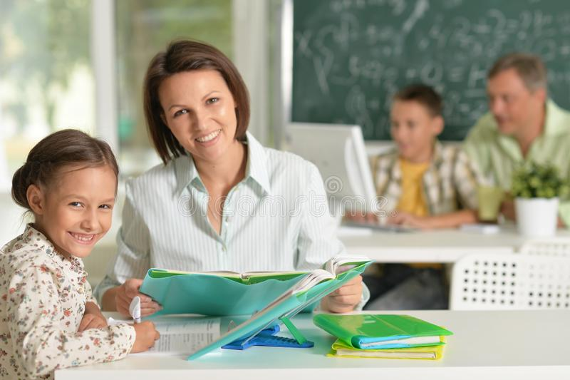 Portrait of experienced teachers working with children. Experienced teachers working with children in computer class stock photo