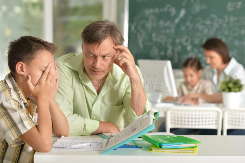 Experienced teachers working with children. In computer class royalty free stock image
