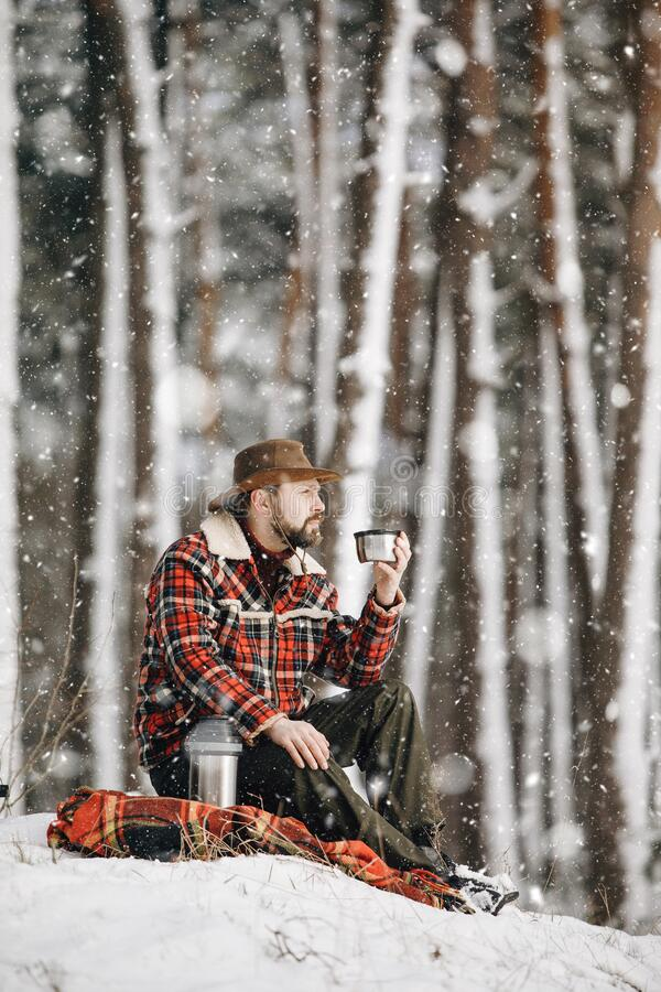 Experienced Tourist in Wide Brim Hat Having a Coffee Halt. On a winter forest edge royalty free stock image