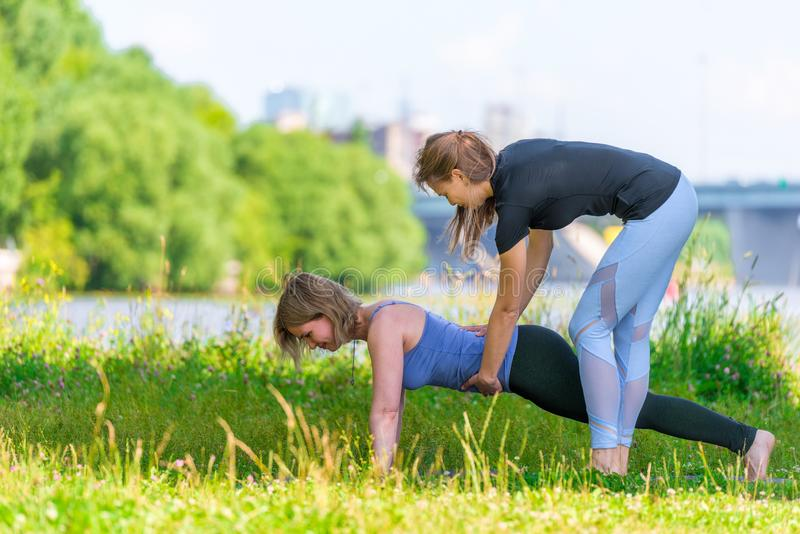 An experienced trainer practices yoga on an individual basis, outdoor sports. In the park stock image