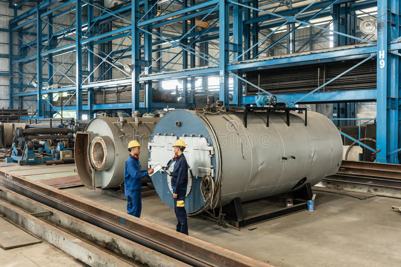 Experienced worker checking the quality of manufactured boilers. Experienced worker writing observations while checking the quality of manufactured industrial royalty free stock photos