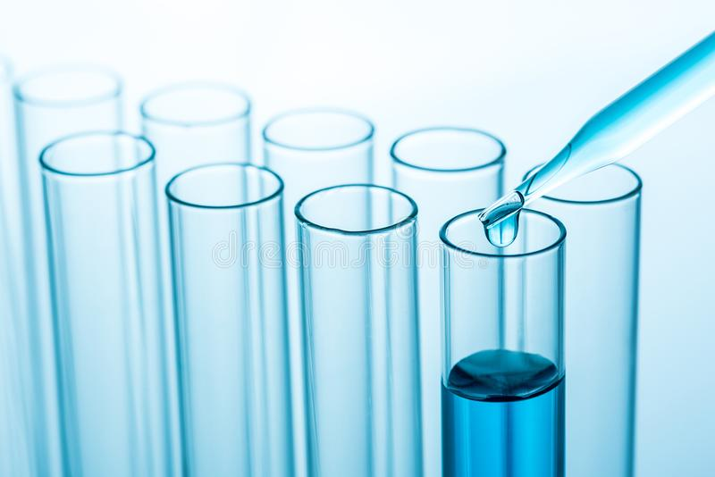 Experimental drops over science laboratory test tubes , science royalty free stock image