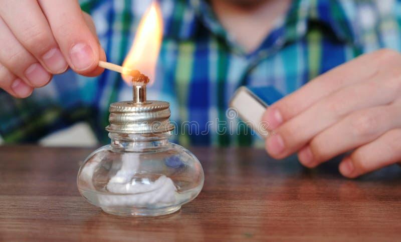 Experimenten op chemie thuis De handen van de close-upjongen ` s plaatst de brandende alcohollamp op brand met een gelijke stock foto's