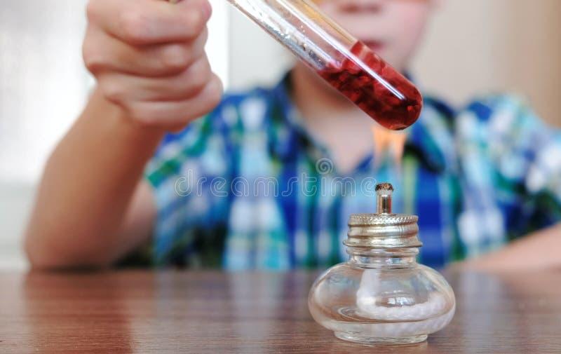 Experimenten op chemie thuis De handen van de close-upjongen ` s verwarmt de reageerbuis met rode vloeistof bij het branden van a stock afbeeldingen