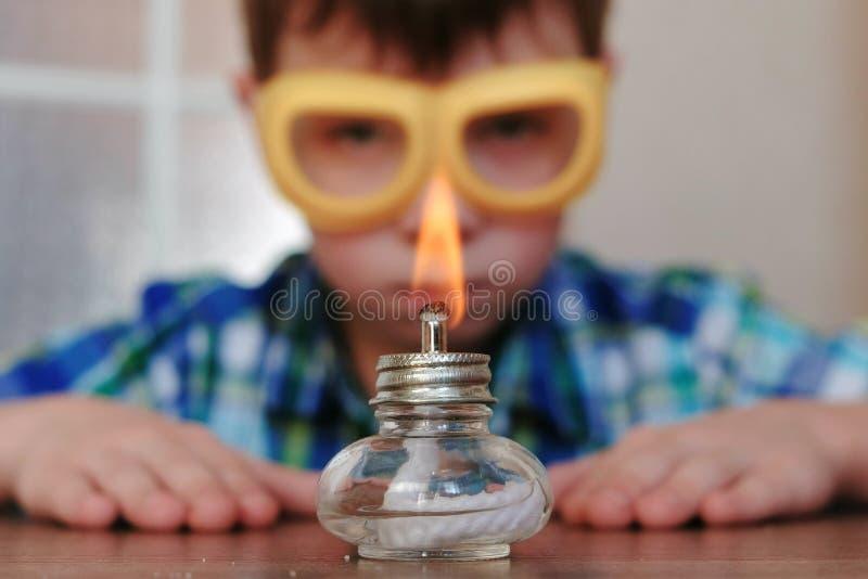 Experimenten op chemie thuis De jongen bekijkt de brandende alcohollamp op brand met een gelijke royalty-vrije stock fotografie