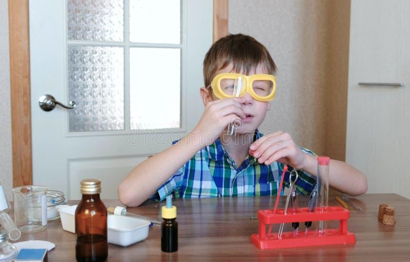 Experimenten op chemie thuis De jongen bekijkt buis om het ervoor te zorgen schone ` s royalty-vrije stock fotografie