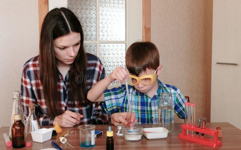 Experimenten op chemie thuis De moeder en de zoon doen samen een wetenschapsexperiment royalty-vrije stock afbeeldingen