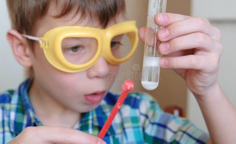 Experimenten op chemie thuis Het gezicht van de close-upjongen ` s Chemische reactie met de versie van gas in een reageerbuis in royalty-vrije stock foto's