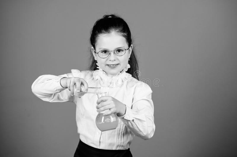 Experimenting a bit. Small kid study. Education concept. Basic knowledge. Knowledge day. Serious about studying. Schoolgirl with chemical liquids. Childhood royalty free stock photos