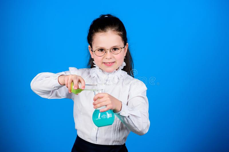 Experimenting a bit. Small kid study. Education concept. Basic knowledge. Knowledge day. Serious about studying. Schoolgirl with chemical liquids. Childhood stock image