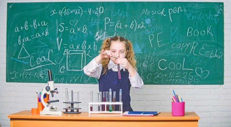 Experimento elegante de la escuela de la conducta del estudiante de la muchacha L?quidos qu?micos del estudio del alumno de la es fotos de archivo
