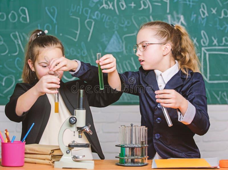 experimentos de la ciencia en laboratorio Investigaci?n de la qu?mica Ni?os que usan el microscopio Ni?as en escuela Microscopio imagen de archivo libre de regalías
