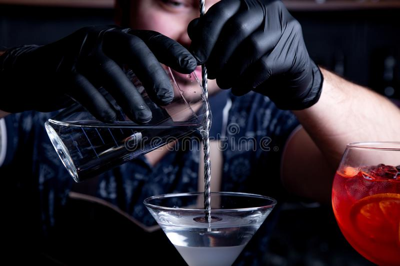 Expert barman is making cocktail at night club. Professional bartender at work in bar pouring sweet drink into glass on stock photography