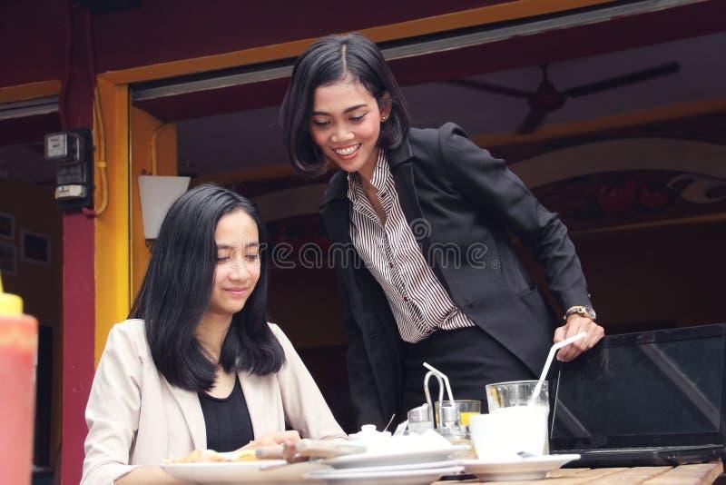 Expert businesswoman supervising in restaurant. Expert business women checking on her working associate activity in a restaurant stock image