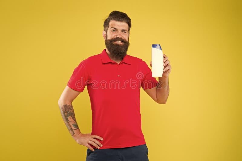 Expert care for demanding hair. Shampoo for hair type. Make hair stronger. Man handsome bearded hipster hold bottle stock image