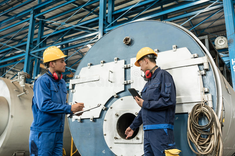 Expert checking the quality of manufactured boilers. Asian expert checking the quality requirements of manufactured industrial steam boilers stock images