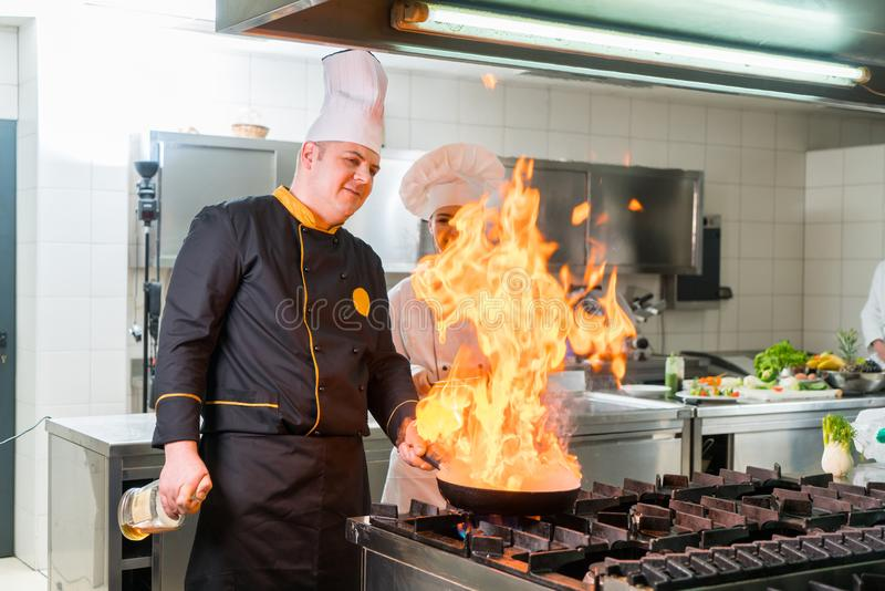 Expert chef preparing meal while giving his assistant tips. stock photos