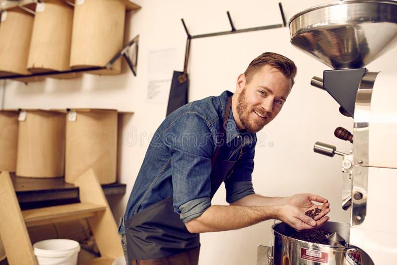 Expert en matière de café vérifiant les grains de café fraîchement rôtis dans le mA moderne images stock