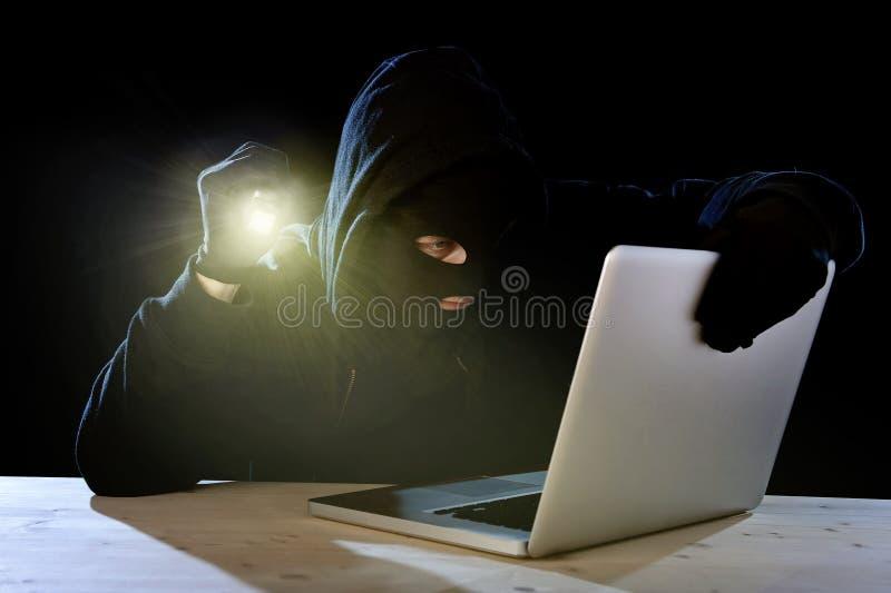 Expert hacker with computer laptop holding flashlight hacking system. Hacker man in black hood and mask with computer laptop holding flashlight in dangerous dark royalty free stock photo