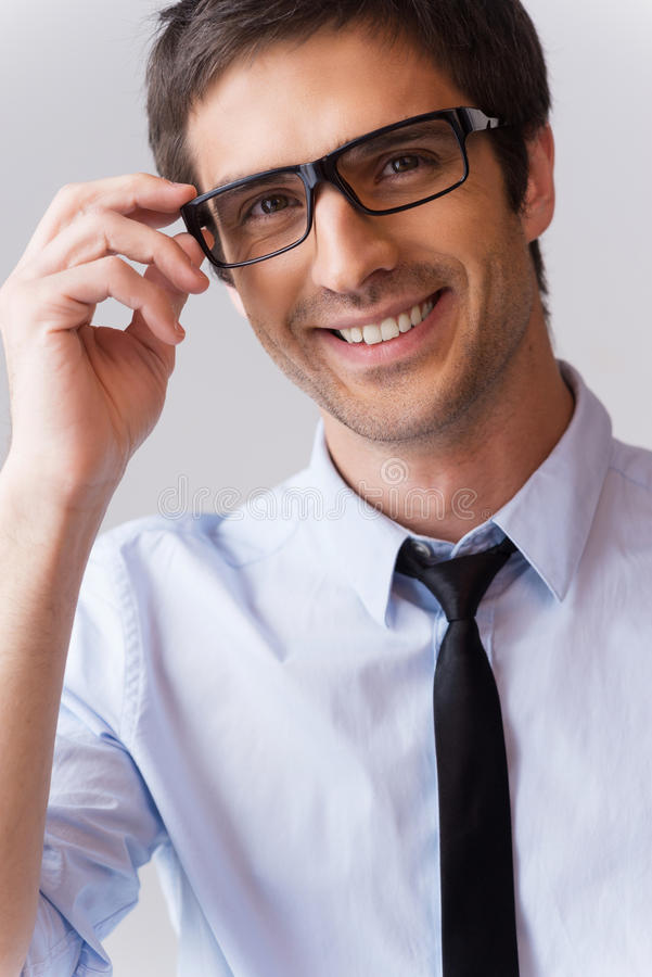 Expert look. Portrait of handsome young man in shirt and tie adjusting his eyeglasses and smiling while standing against grey background stock photography