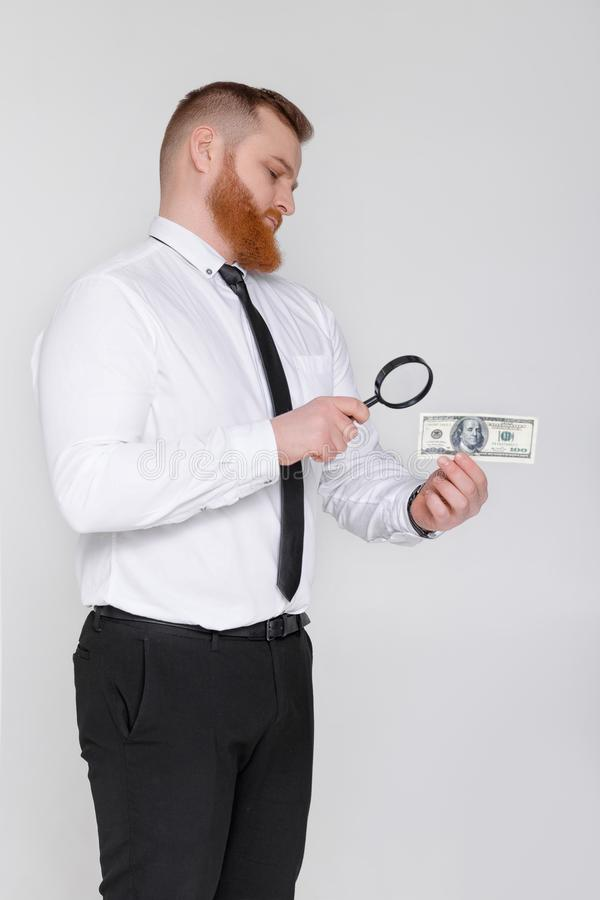 Expert looking at magnifying glass for bill stock photography