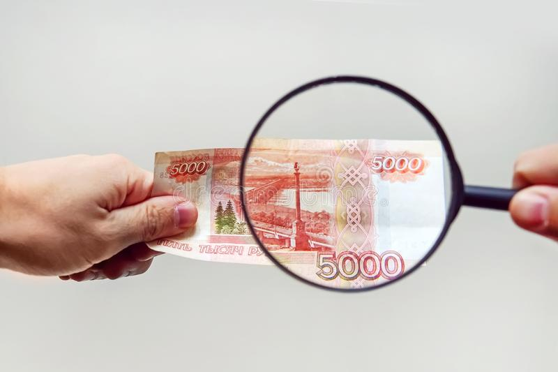 Expert with magnifying glass checks suspicious money. Search watermarks on paper of the fake bills. magnifying glass, magnifier, magnifying lens, magnifying royalty free stock image