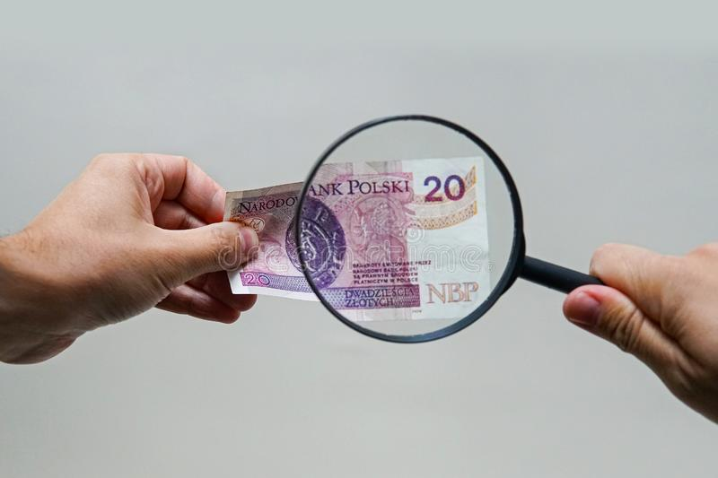 Expert with magnifying glass checks suspicious money. Search watermarks on paper of the fake bills. magnifying glass, magnifier, magnifying lens, magnifying stock images