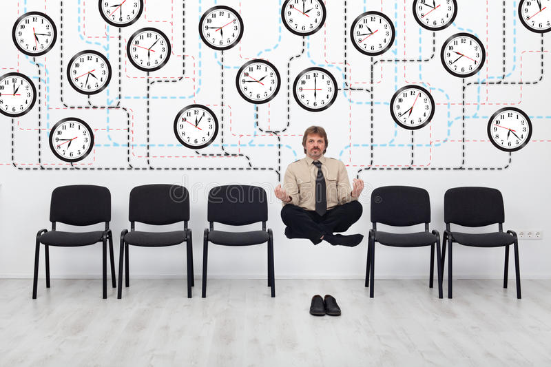 Expert time management. Businessman controlling lots of wall clocks stock photo