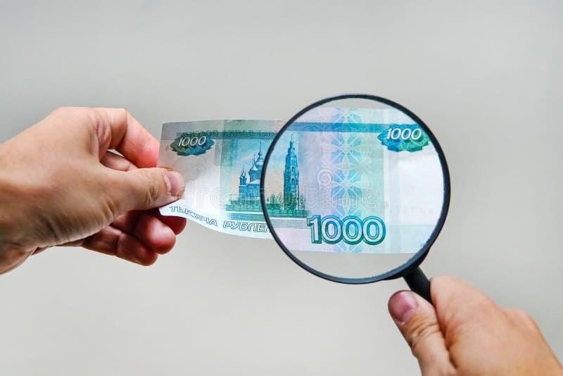 Experte mit Lupe überprüft misstrauisches Geld stockbilder