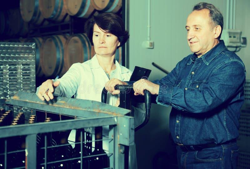 Experten- und Weinhersteller kontrollieren Behälter lizenzfreie stockfotos