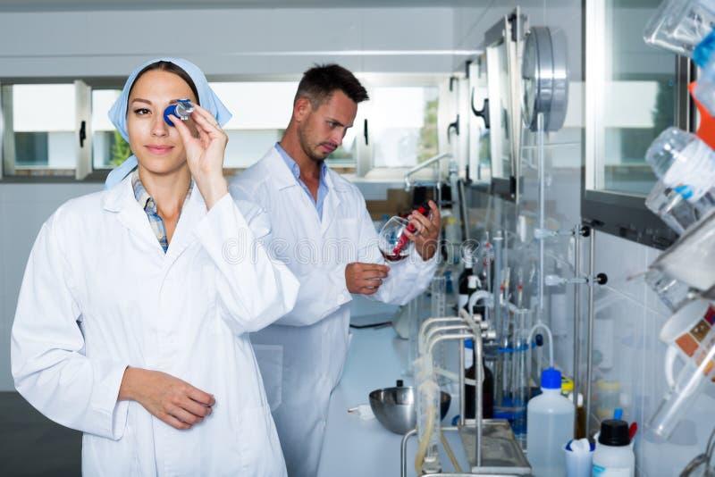 Experto de la mujer en el vino blanco de la prueba de la capa en laboratorio de química foto de archivo
