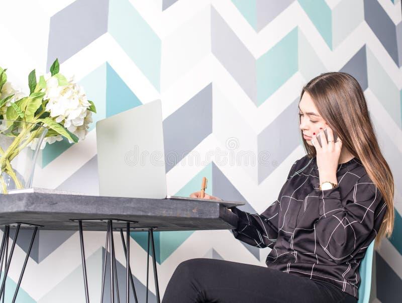 Experto femenino de la planificación de empresas que llama vía celllphone imagenes de archivo