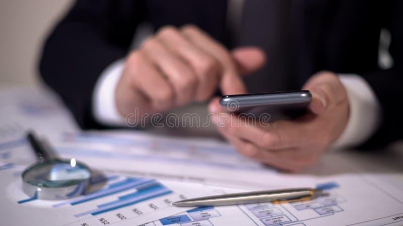 Experto financiero que hace cálculos en el artilugio, estudiando estadísticas en diagramas imagenes de archivo