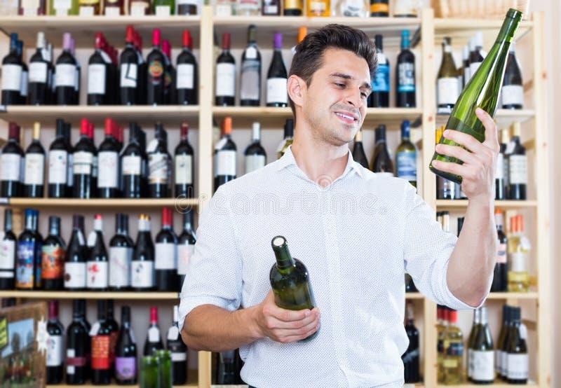 Experto masculino del vino que sostiene las botellas de vino en la sección del lagar imagenes de archivo