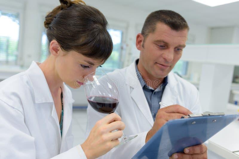 Expertos en las capas blancas que comprueban calidad de vino en laboratorio fotografía de archivo libre de regalías