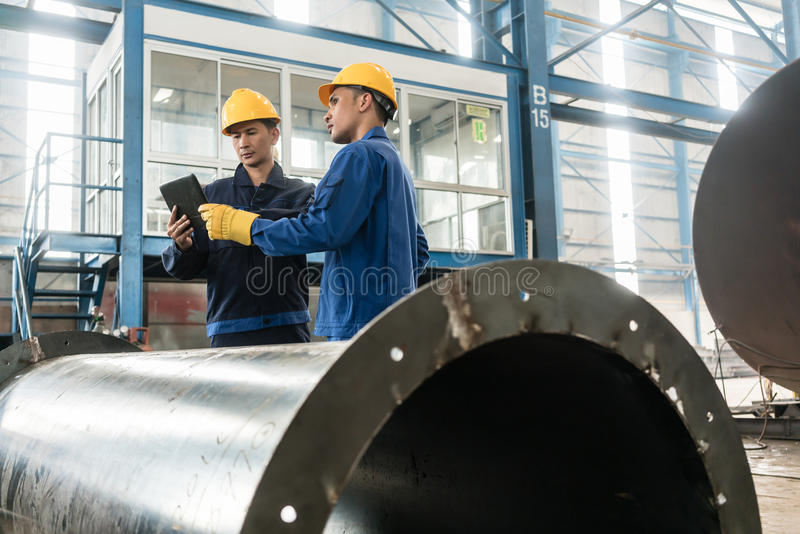 Experts checking information on tablet PC in a modern factory royalty free stock photo
